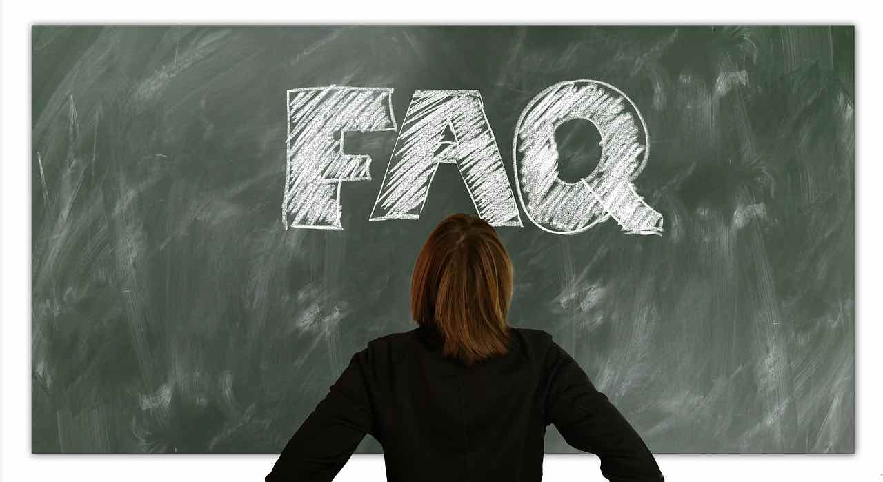 Female looking at a blackboard where FAQ is written in chalk.