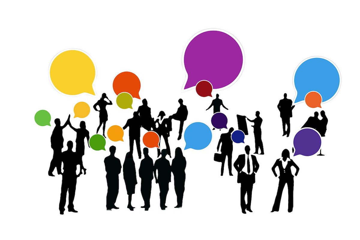 Many different silhouettes with speech bubbles indicating talking, feedback and work of mouth marketing.